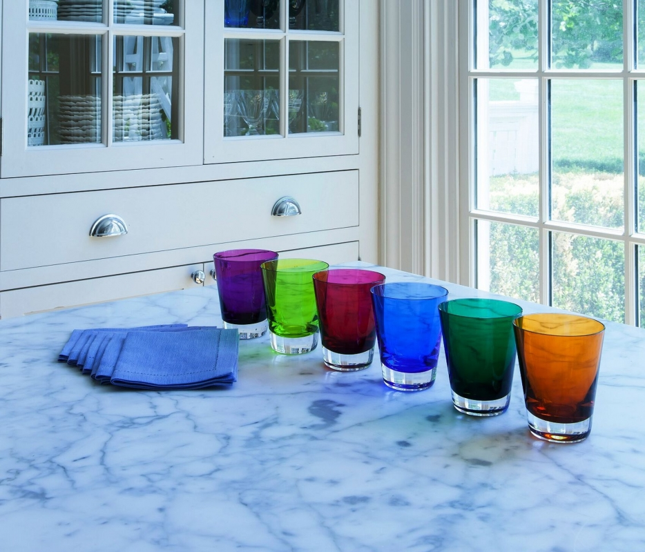 MOSAÏQUE tumblers set. Handcrafted using traditional glassblowing techniques, these glasses are the perfect gift! Available in a set of 6 in 6 different colors. The tableware has a simple silhouette that is precise and elegant. The understated shape of the tumblers makes their use appropriate for any and all drinking experiences: as a water or fruit juice glass, or mixed in with Baccarat clear crystal bar sets. The hand-blown MOSAÏQUE tumblers are cased in clear crystal, and are available in a vast array of cheerful colors in this set: orange, blue, purple, moss, green, and Baccarat's signature ruby red crystal. The interplay of light with the smooth surface and the colored crystal makes for a radiant table, and a compelling soirée.